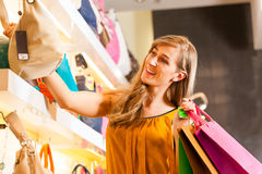 Γυναίκα που αγοράζει μια τσάντα στη λεωφόρο Στοκ Εικόνα