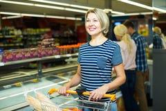 Γυναίκα που αγοράζει τα παγωμένα λαχανικά Στοκ Φωτογραφίες