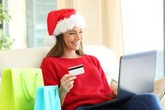 Γυναίκα που αγοράζει τα σε απευθείας σύνδεση δώρα Χριστουγέννων Στοκ Εικόνες