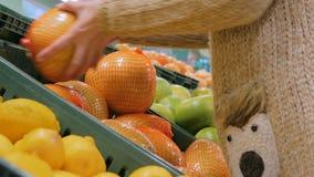 Γυναίκα που αγοράζει τα φρέσκα εξωτικά εσπεριδοειδή στο μανάβικο φιλμ μικρού μήκους