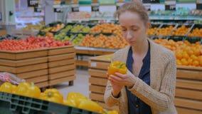 Γυναίκα που αγοράζει τα φρέσκα πορτοκαλιά πιπέρια κουδουνιών στο μανάβικο απόθεμα βίντεο