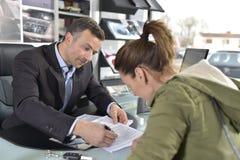 Γυναίκα που αγοράζει τον έμπορο αυτοκινήτων μορφής αυτοκινήτων Στοκ Εικόνες