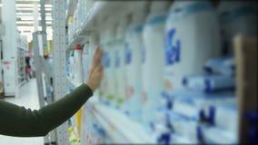 Γυναίκα που αγοράζει το υγρό απορρυπαντικό πλυντηρίων στην υπεραγορά φιλμ μικρού μήκους