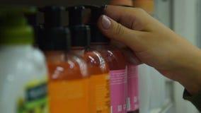 Γυναίκα που αγοράζει το υγρό σαπούνι στην υπεραγορά απόθεμα βίντεο