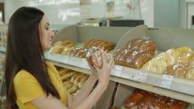 Γυναίκα που αγοράζει το φρέσκο ψωμί μέσα στο μανάβικο απόθεμα βίντεο