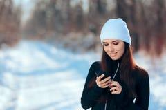 Γυναίκα που ακούει η αγαπημένη μουσική της Playlist ασκώντας στη χειμερινή εποχή Στοκ εικόνες με δικαίωμα ελεύθερης χρήσης