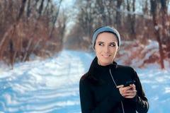 Γυναίκα που ακούει η αγαπημένη μουσική της Playlist ασκώντας στη χειμερινή εποχή Στοκ Φωτογραφίες