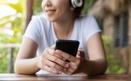 Γυναίκα που ακούει τη μουσική με το ακουστικό και το έξυπνο τηλέφωνο στοκ φωτογραφίες