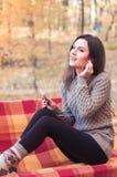 Γυναίκα που ακούει τη μουσική σε έναν πάγκο Στοκ Φωτογραφία