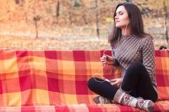 Γυναίκα που ακούει τη μουσική σε έναν πάγκο Στοκ Εικόνες