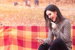 Γυναίκα που ακούει τη μουσική σε έναν πάγκο Στοκ Φωτογραφίες