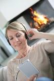 Γυναίκα που ακούει τη χαλάρωση μουσικής από την εστία Στοκ φωτογραφίες με δικαίωμα ελεύθερης χρήσης