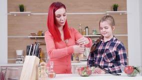 Γυναίκα που αλατίζει τη σαλάτα ενώ η κόρη της εξετάζει την απόθεμα βίντεο