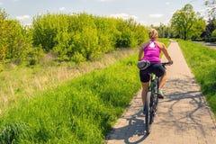 Γυναίκα που ανακυκλώνει ένα ποδήλατο βουνών στο πάρκο πόλεων, θερινή ημέρα στοκ εικόνες