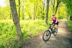 Γυναίκα που ανακυκλώνει ένα ποδήλατο βουνών στο πάρκο πόλεων, θερινή ημέρα στοκ φωτογραφία με δικαίωμα ελεύθερης χρήσης