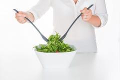 Γυναίκα που αναμιγνύει τη σαλάτα arugula στο τετραγωνικό κύπελλο Στοκ εικόνα με δικαίωμα ελεύθερης χρήσης