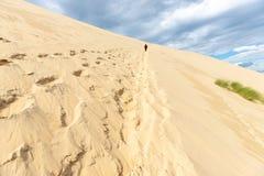 Γυναίκα που αναρριχείται στον αμμόλοφο Pyla στοκ εικόνες