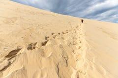 Γυναίκα που αναρριχείται στον τεράστιο αμμόλοφο άμμου Pyla στοκ εικόνα με δικαίωμα ελεύθερης χρήσης