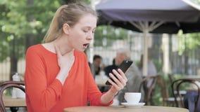 Γυναίκα που ανατρέπεται νέα από την απώλεια σε Smartphone, που κάθεται στο πεζούλι καφέδων απόθεμα βίντεο