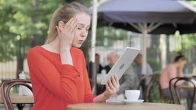 Γυναίκα που ανατρέπεται νέα από την απώλεια στην ταμπλέτα, που κάθεται στο πεζούλι καφέδων απόθεμα βίντεο