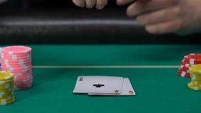 Γυναίκα που ανοίγει τις κάρτες της και που βάζει ένα ζευγάρι των άσσων στον πίνακα, που παίζει το πόκερ απόθεμα βίντεο