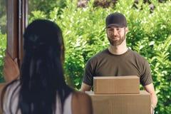 Γυναίκα που απαντά στην πόρτα σε έναν deliveryman Στοκ Εικόνα