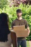 Γυναίκα που απαντά στην πόρτα σε έναν deliveryman Στοκ Εικόνες