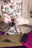 Γυναίκα που απασχολείται στα headdress Ράβοντας λουλούδι του υφάσματος Στοκ Εικόνες