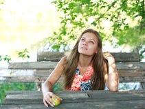 Γυναίκα που απολαμβάνει μια θερινή ημέρα στον ξύλινο πάγκο στοκ φωτογραφία με δικαίωμα ελεύθερης χρήσης