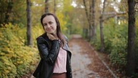 Γυναίκα που απολαμβάνει την ημέρα φθινοπώρου, αυτή που περπατά στο πάρκο, ζωηρόχρωμο φύλλωμα γύρω φιλμ μικρού μήκους