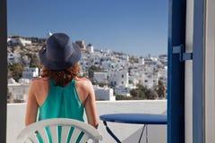 γυναίκα που απολαμβάνει την πόλης θέα mykonos από το πεζούλι, Ελλάδα - καλοκαιρινές διακοπές στοκ φωτογραφίες
