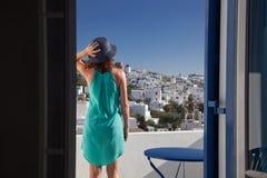 γυναίκα που απολαμβάνει την πόλης θέα mykonos από το πεζούλι, Ελλάδα - καλοκαιρινές διακοπές στοκ εικόνες