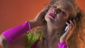 Γυναίκα που απολαμβάνει τη μουσική στα ακουστικά με τις ιδιαίτερες προσοχές απόθεμα βίντεο