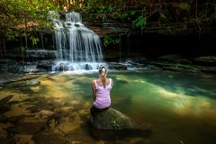 Γυναίκα που απολαμβάνει τη φύση Διάστικτο φως του ήλιου στη λίμνη βράχου καταρρακτών στοκ φωτογραφία με δικαίωμα ελεύθερης χρήσης
