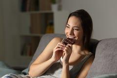 Γυναίκα που απολαμβάνει τρώγοντας τη σοκολάτα στη νύχτα στοκ εικόνες