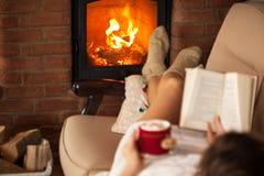Γυναίκα που απολαμβάνεται το ελεύθερο χρόνο από την πυρκαγιά - που διαβάζει ένα βιβλίο Στοκ Εικόνα