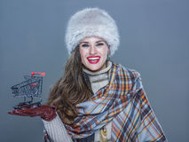 Γυναίκα που απομονώνεται στο κρύο μπλε υπόβαθρο που παρουσιάζει καροτσάκι αγορών Στοκ Εικόνες