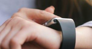 Γυναίκα που αποτελεί τις χειρονομίες σε μια φορετή συσκευή υπολογιστών smartwatch, έξυπνο ρολόι κοντά 4k απόθεμα βίντεο