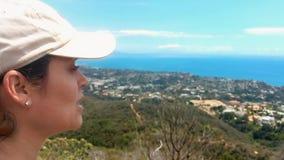 Γυναίκα που απολαμβάνει μια όμορφη θέα του ωκεανού και των βουνών σε Καλιφόρνια απόθεμα βίντεο