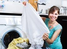 Γυναίκα που απολαμβάνει τα καθαρά ενδύματα μετά από το πλυντήριο Στοκ Φωτογραφία