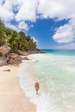 Γυναίκα που απολαμβάνει την τέλεια παραλία εικόνων Anse Patates στο νησί Λα Digue, Σεϋχέλλες Στοκ εικόνα με δικαίωμα ελεύθερης χρήσης