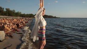 Γυναίκα που απολαμβάνει της ελευθερίας και της ζωής στην παραλία στο ηλιοβασίλεμα φιλμ μικρού μήκους
