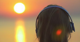 Γυναίκα που απολαμβάνει τη μουσική και το ηλιοβασίλεμα απόθεμα βίντεο