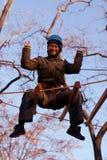Γυναίκα που απολαμβάνει τη δραστηριότητα σε ένα πάρκο σχοινιών Στοκ Εικόνες