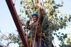 Γυναίκα που απολαμβάνει τη δραστηριότητα σε ένα πάρκο σχοινιών Στοκ Εικόνα