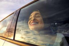 Γυναίκα που απολαμβάνει cloudscape το κοίταγμα μέσω του παραθύρου αυτοκινήτων Στοκ Φωτογραφίες