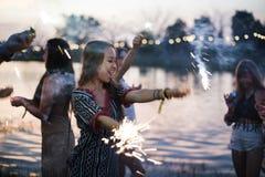 Γυναίκα που απολαμβάνει Sparkler στο γεγονός φεστιβάλ Στοκ Εικόνες