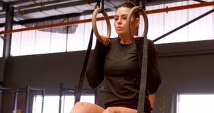 Γυναίκα που ασκεί με τα γυμναστικά δαχτυλίδια στο στούντιο 4k ικανότητας απόθεμα βίντεο