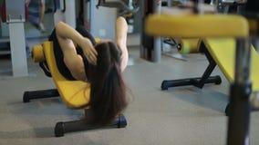 Γυναίκα που ασκεί το κάθομαι-UPS στις μηχανές άσκησης στη γυμναστική απόθεμα βίντεο