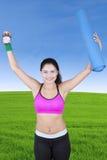 Γυναίκα που αυξάνει τα χέρια με το ρολόι και το χαλί στοκ εικόνες με δικαίωμα ελεύθερης χρήσης